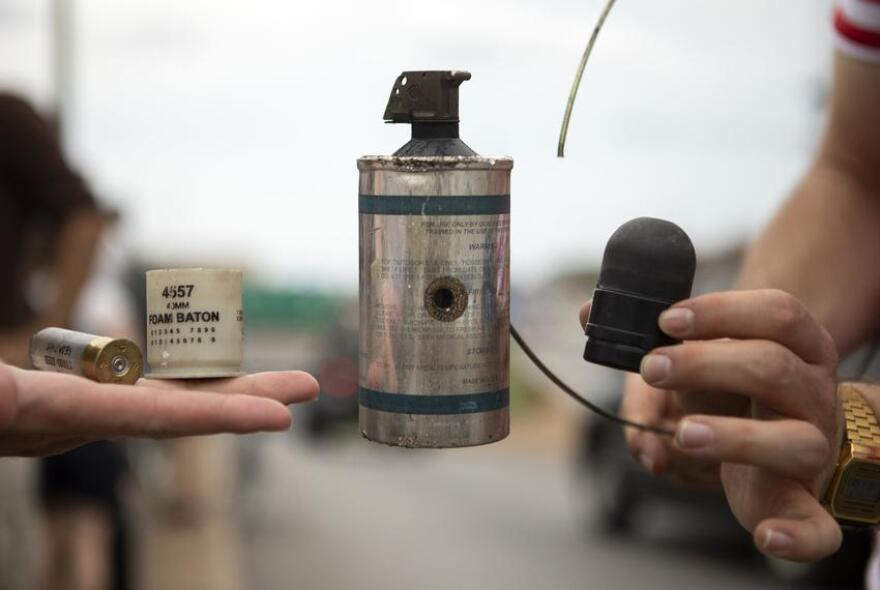 Bean bag shells, a canister and a rubber bullet are held up after Austin police forced protesters from Interstate 35 Sunday.