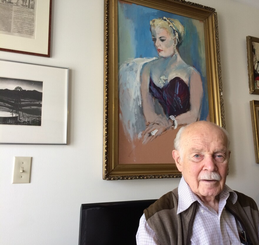James Benner at his apartment in Morgantown. On the wall behind him is a portrait of his late wife, Frances Yeend, as well as a few items he's keeping from their shared collection.