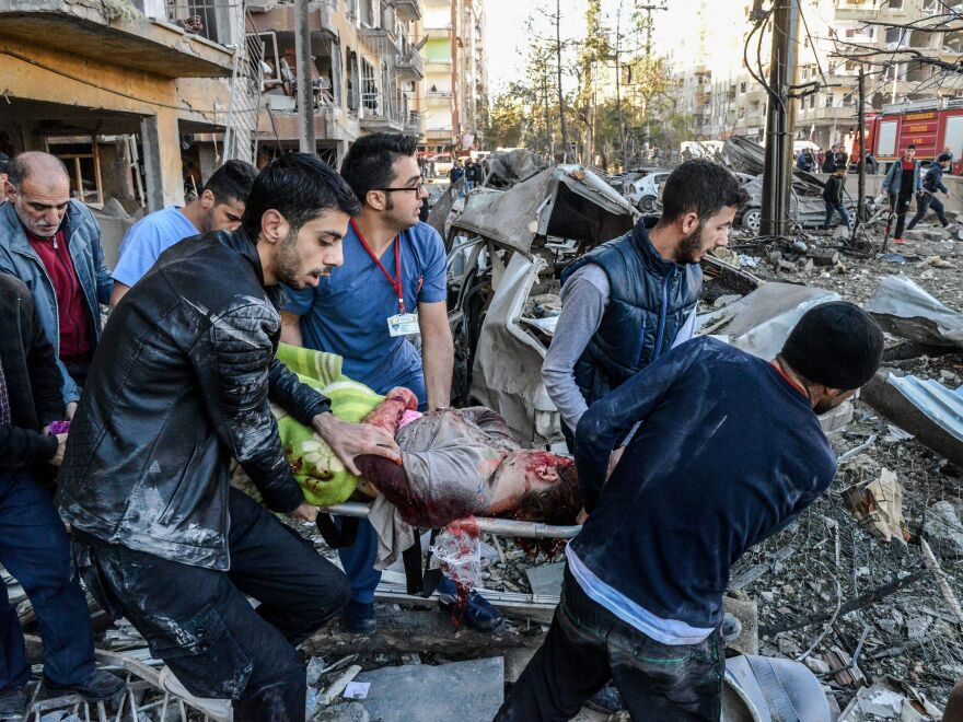 Rescue officials and others carry an injured man from the explosion site after a car bomb detonated in the southeastern Turkish city of Diyarbakir. At least eight people were killed and 100 injured in a blast outside a police building Friday morning.