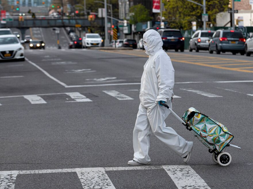 A woman wearing a hazmat suit pulls her grocery cart in the streets in New York City amid the coronavirus pandemic.