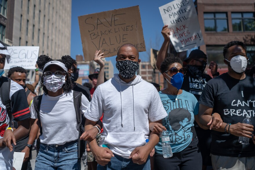 Jason Barney, center, locks arms with fellow protester Sunday June 7, 2020, in downtown St. Louis. He was among thousands who continued days of protests against police brutality.