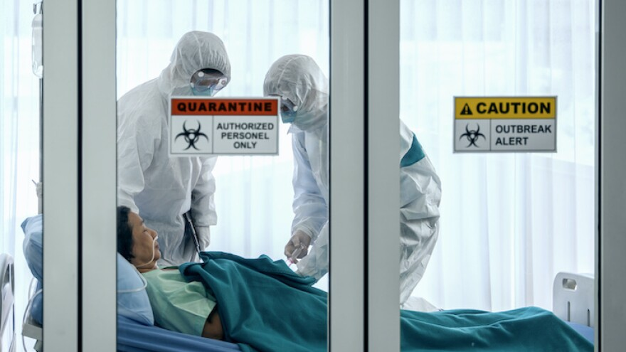 covid-19 infected patient on bed in quarantine room with quarantine and breakout alert sign at hospital with disease control experts try to make disease treatment
