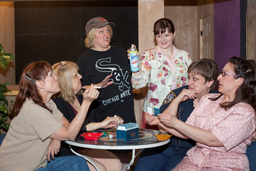 """Olive, played by Kim Furlow, and Florence, played by Colleen Backer, both standing, surrounded by friends, in in Dramatic License's """"The Odd Couple"""""""