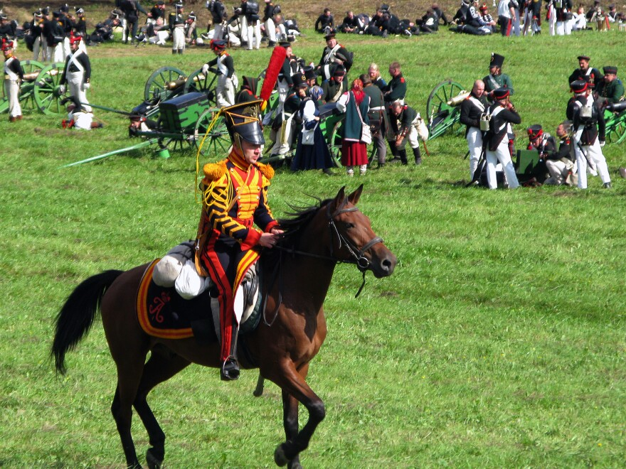 A Russian hussar races past the artillery as the battle is about to begin.
