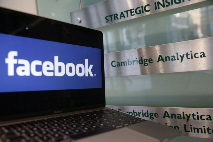 A laptop showing the Facebook logo is held alongside a Cambridge Analytica sign at the entrance to the London offices of Cambridge Analytica. The company's acting CEO, Alexander Tayler, is stepping down, and is the second CEO out since the data sharing scandal broke.