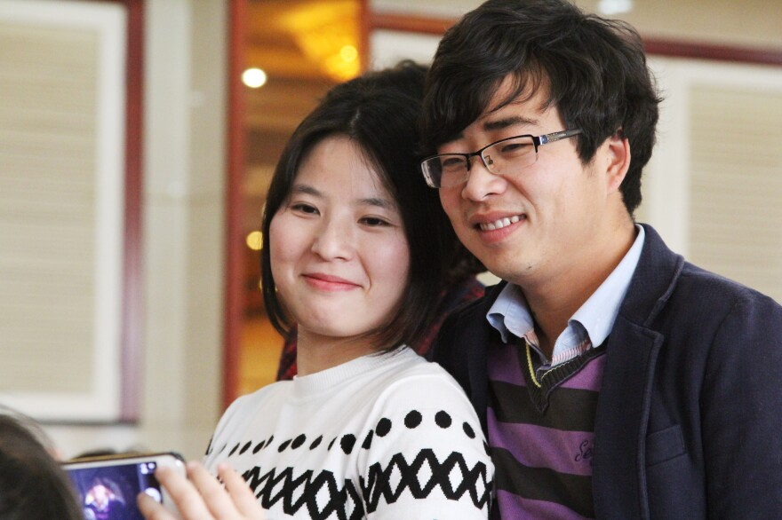 Zhang Zhaojun, 26, attends her brother's wedding with her boyfriend, Chen Ke. Zhao used to assemble computer motherboards in southern China. Now she's back home in Qichun, in Hubei province, making more money working as an accountant at a fertilizer factory.