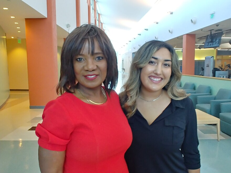 African American woman and female Hispanic student pose for a photo.