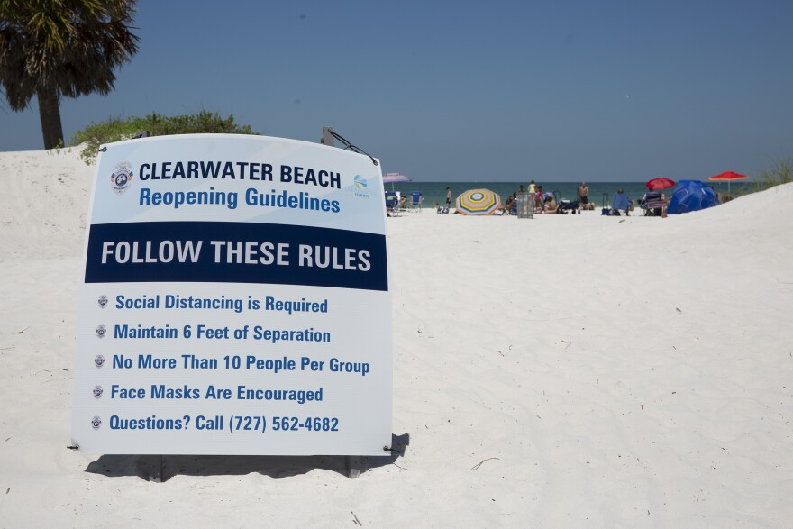 A sign on the beach says groups of more than 10 shouldnt gather and face masks are encouraged.