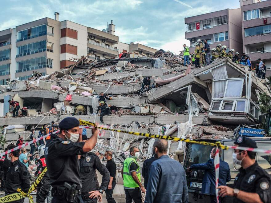 Rescuers search for survivors in a collapsed building in Izmir, Turkey, after a powerful earthquake struck Turkey's western coast and parts of Greece Friday.