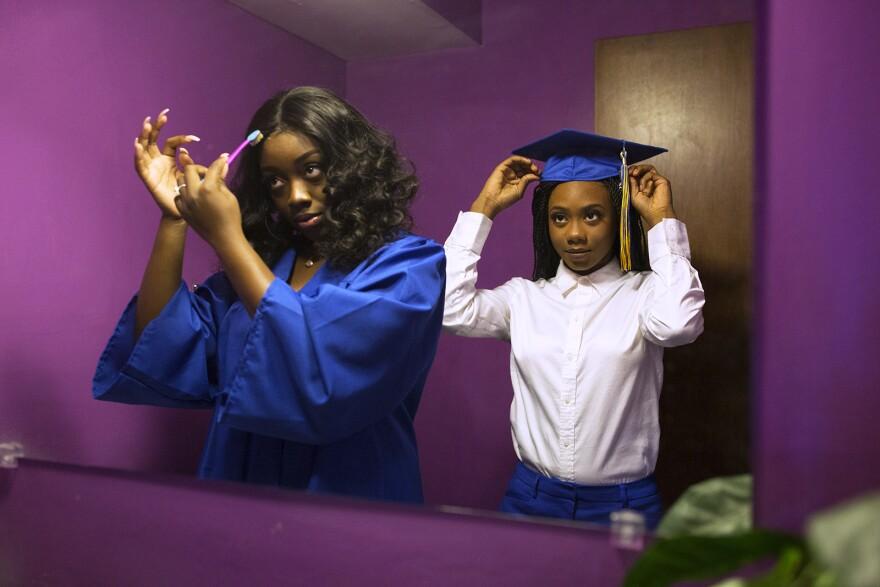 Ngone, right, gets ready for graduation alongside her friend Sierra Cody.