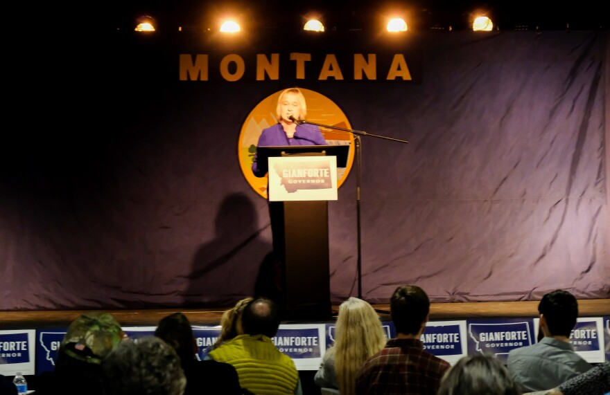 Kristen Juras stands at a podium in front of the Montana flag