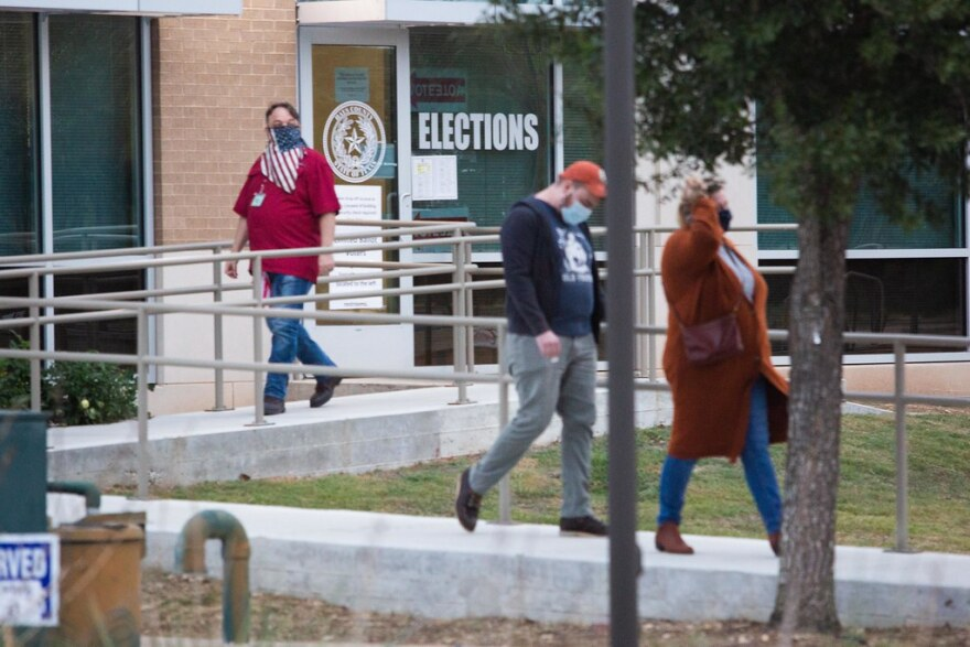 People wearing face coverings leave the Hays County Government Center building, an early voting site in Hays County.