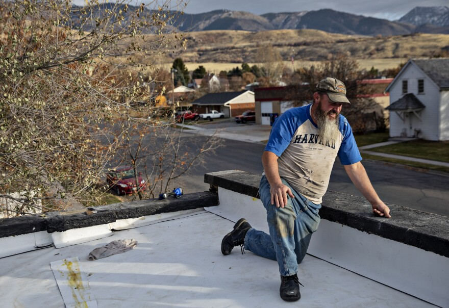 A man kneels on a roof.