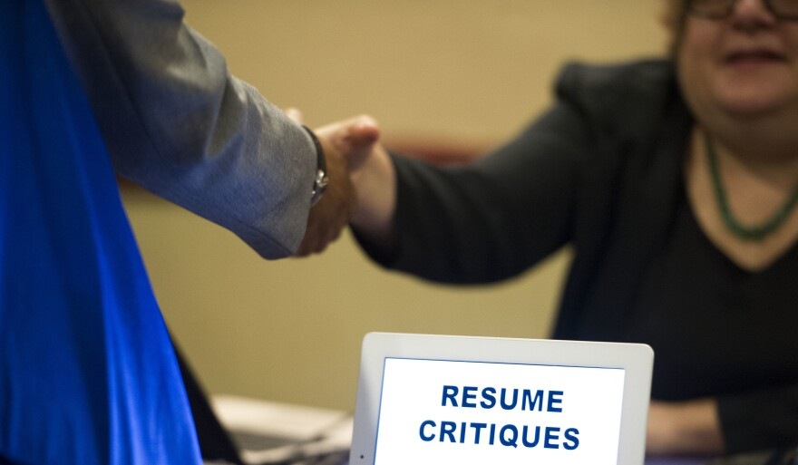 A job seeker stops at a table offering resume critiques during a job fair held in Atlanta.