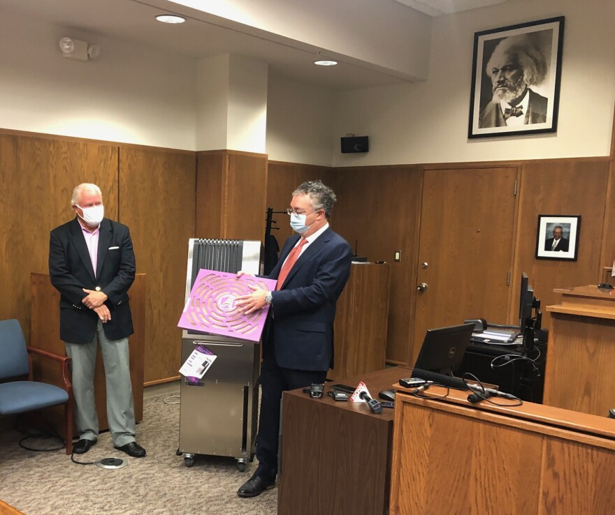 Aerobiotix President Dr. David Kirschman shows reporters a filter from the ILLUVIA 500 UV machine during a demonstration yesterday at the courthouse. Judge Steve Dankoff watches on the left.