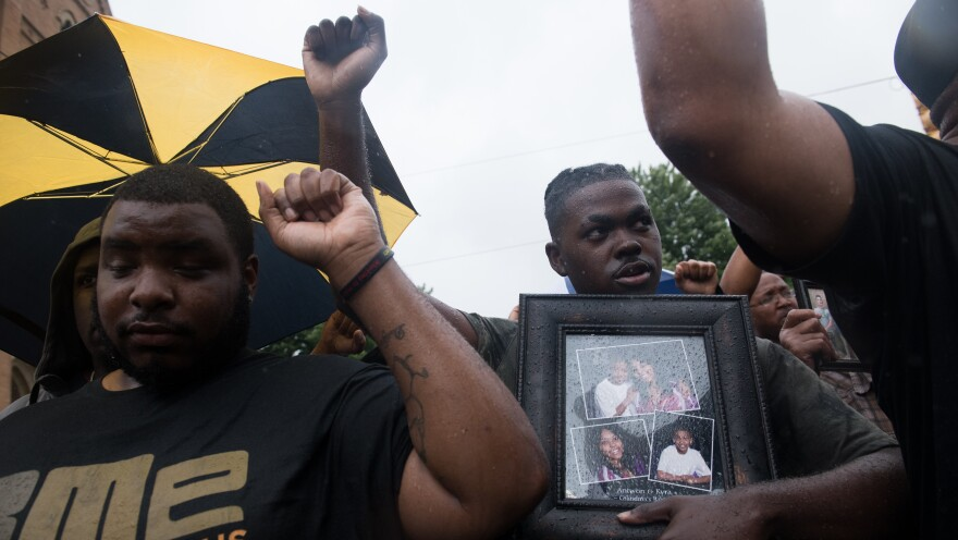 A man holds a photo of Antwon Rose during a June 2018 protest in Pittsburgh. Former East Pittsburgh police officer Michael Rosfeld shot and killed 17-year-old Rose as the teen ran from a car the officer had pulled over, sparking protests across the city.