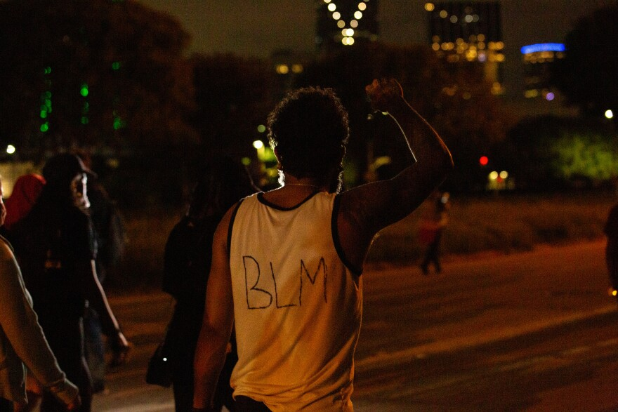 Photo of protester with BLM written on the back of his sleeveless shirt walking down S Lamar St. in Dallas.