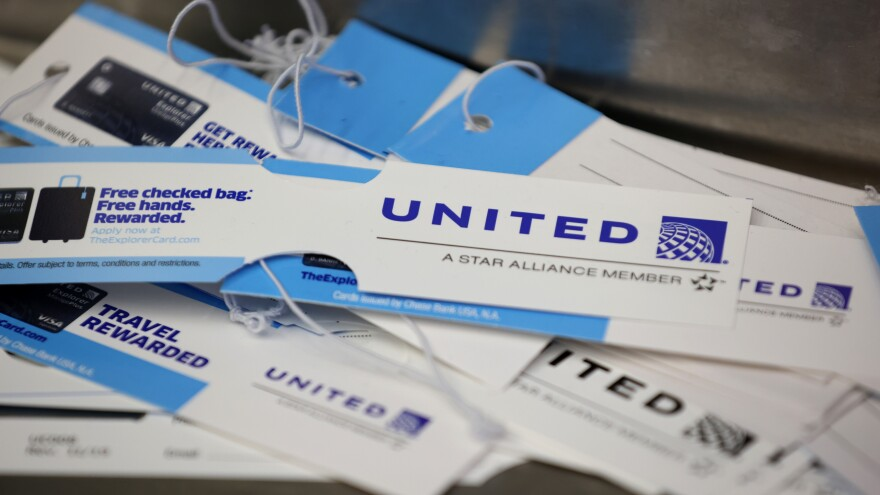 United Airlines baggage tags are displayed on a table at San Francisco International Airport. The carrier says it's starting a pilot program next month that will offer rapid coronavirus testing at the airport or via a self-collected, mail-in test ahead of a flight.