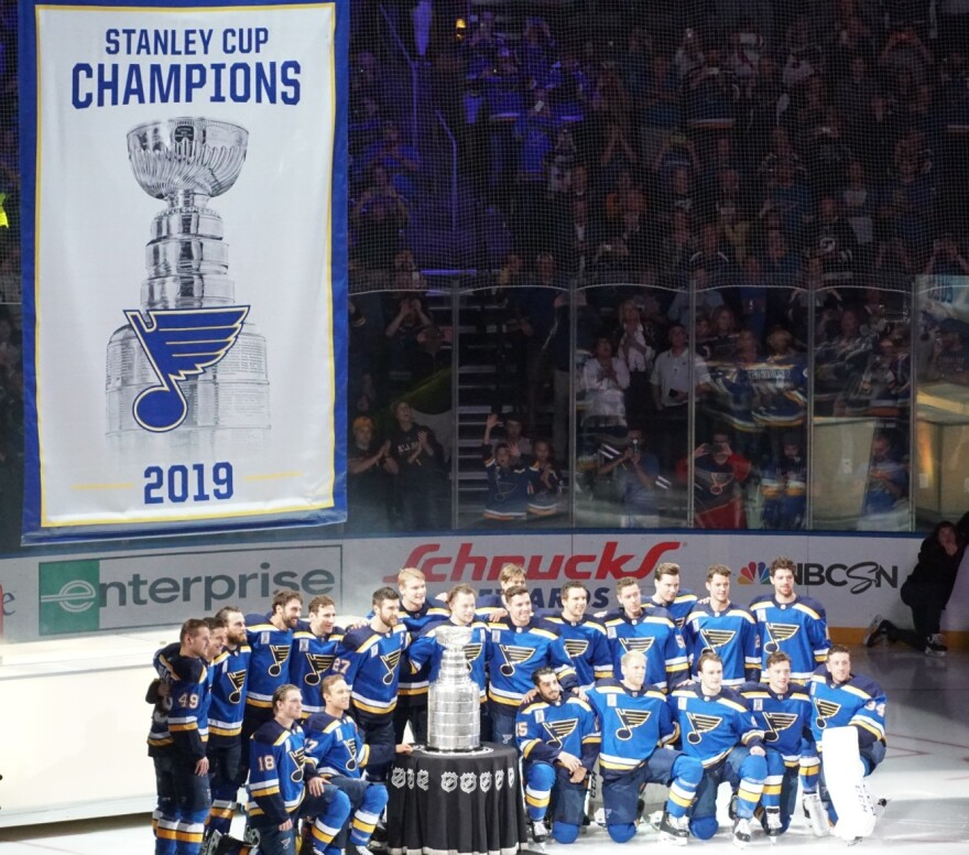St. Louis Blues players huddle around the Stanley Cup during the banner raising ceremony.
