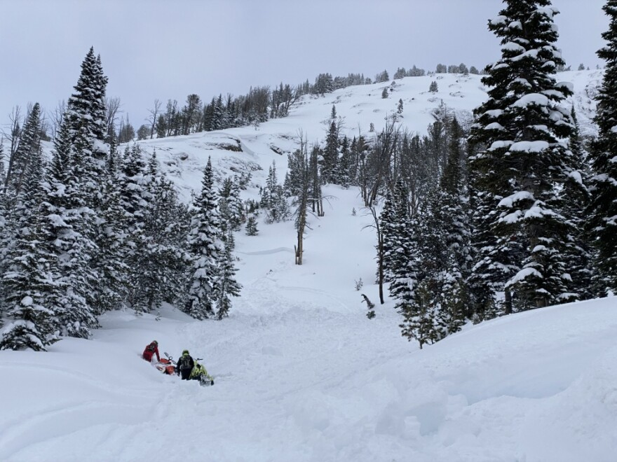 Two snowmobilers are waist deep in mountain snow with their snowmobiles on Mt. Abundance.