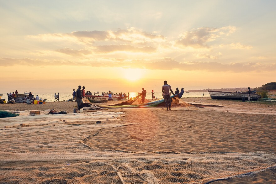 Shortly after dawn, fishermen untangle and lay out their nets at Makawa beach on Lake Malawi.