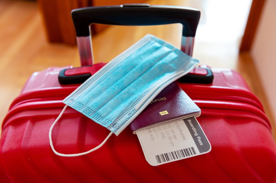 Face protection mask and travel documents over trolley bag. Travel and flight rules during coronavirus pandemic crisis. (Getty Images)