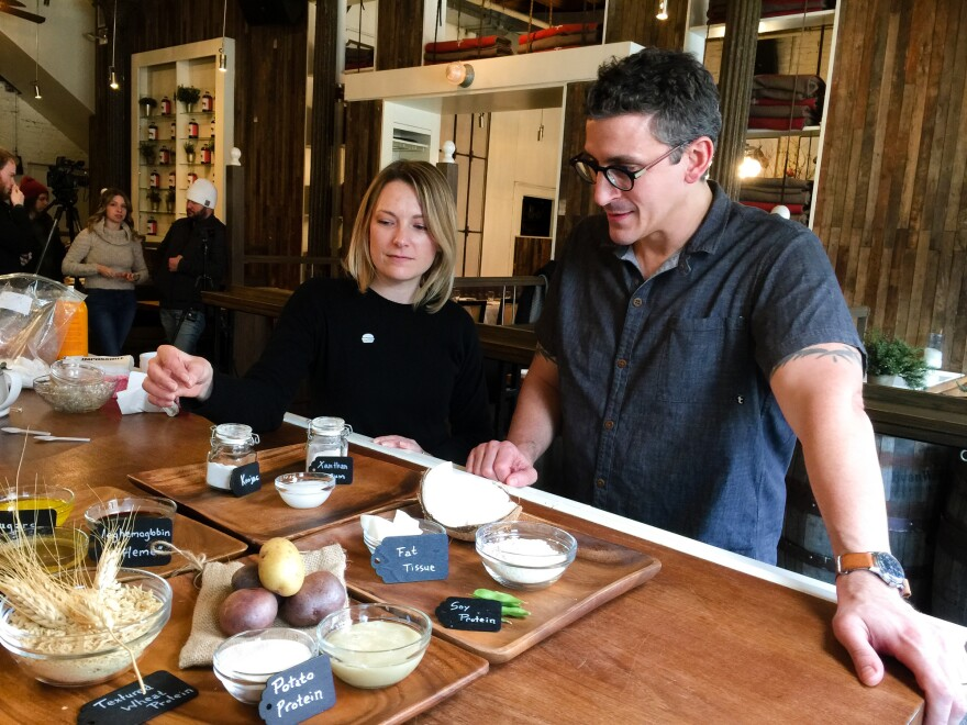 Ashley Kleckner of Impossible Foods demonstrates to chef Brad Farmerie how the Impossible Burger is assembled.