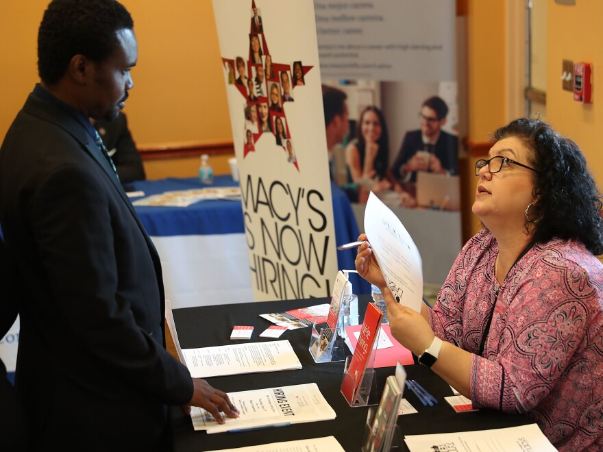 Betty Fernandez of Macy's department store speaks with a potential applicant about job openings during a job fair in Miami on April 5. Employers added far more jobs than expected in April — another sign the U.S. economy is chugging along as the expansion nears the 10-year mark.