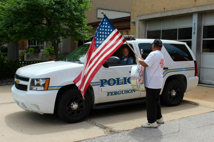 A man with an American flag stands in front of a Ferguson Police car earlier in July. A wide-ranging municipal court bill that takes effect on Friday doesn't impact Ferguson as much as other cities in the St. Louis region. 2015