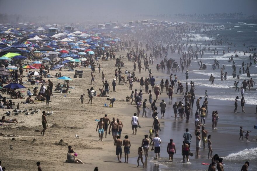 People crowd the beach in Huntington Beach, Calif., as the state swelters under a heat wave.