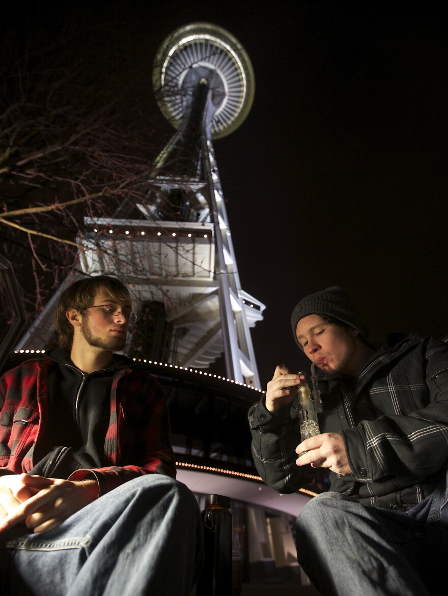 The legalization of marijuana could dry up a revenue stream for police, according to reports. Here, two men share a water pipe underneath the Space Needle shortly after a law legalizing the recreational use of marijuana took effect in Seattle in 2012.