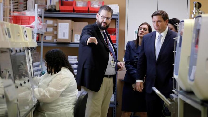 Florida Gov. Ron DeSantis, right, takes a tour of Florida's Bureau of Public Health Laboratories with the Director, Stephen White, where the COVID-19 virus is tested on Monday, March 2, 2020, in Miami.