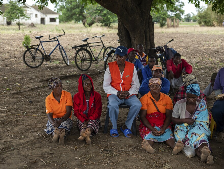 Farmers in the town of Mondiane meet to discuss sustainable farming practices in November. Members of the local disaster preparedness committee wear orange vests with the acronym for the national disaster preparedness agency.