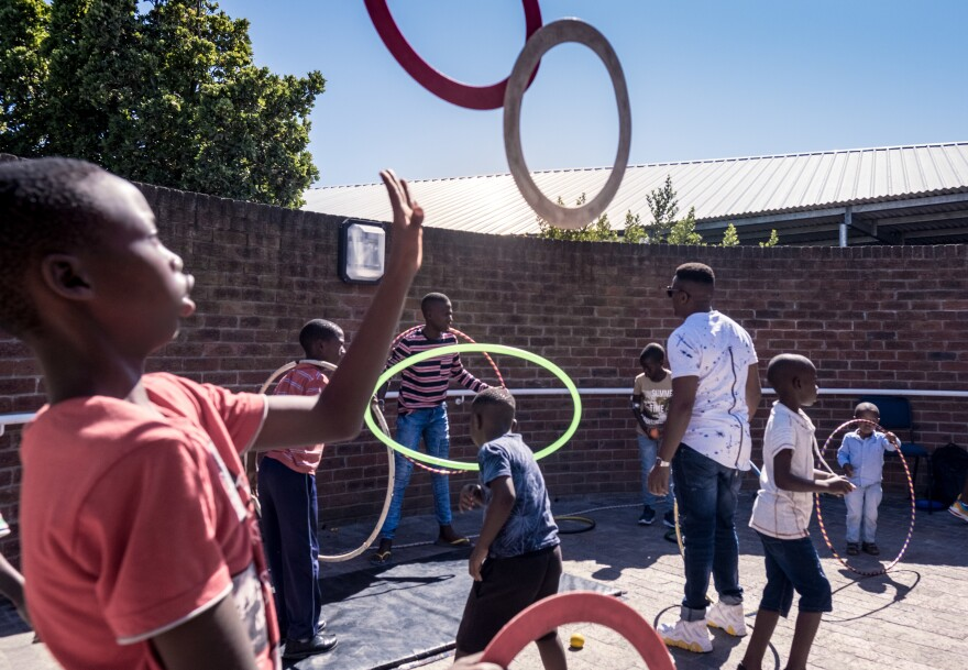 Children who are hospital patients practice circus tricks outside a hospital in the township of Khayelitsha, Cape Town. Zip Zap's Ubuntu program aims to introduce children with medical conditions to the world of circus.
