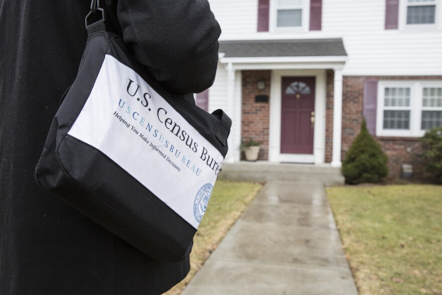 A person carries a bag that says U.S. Census Bureau in front of a house.