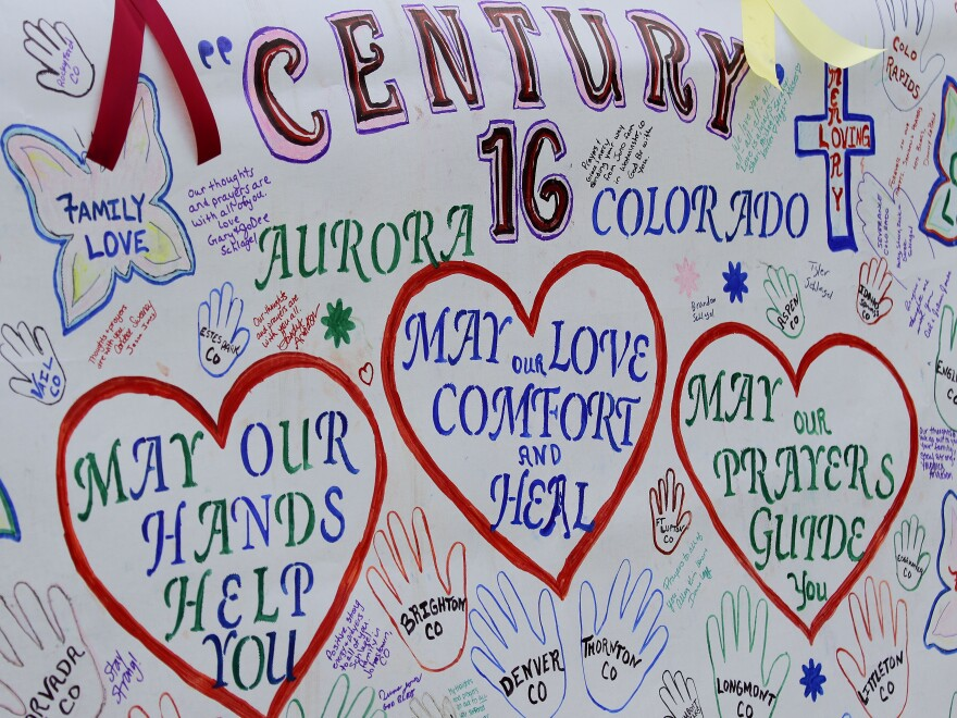 A banner with messages has been put up outside the theaters in Aurora, Colo., where 12 died and 58 were wounded early Friday.