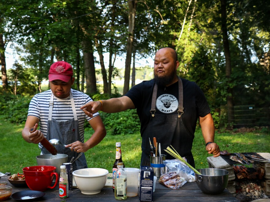 "Chris Her (left) and Yia Vang prepare Hmong style food. ""Every dish has a narrative,"" Vang says, ""and if you follow that narrative closely enough, you understand the people."""