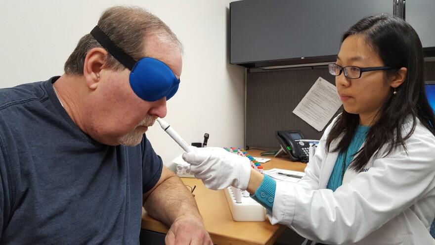 Wash U medical resident Pawina Jiramongkolchai presents Joe Weissmann with a smell test.