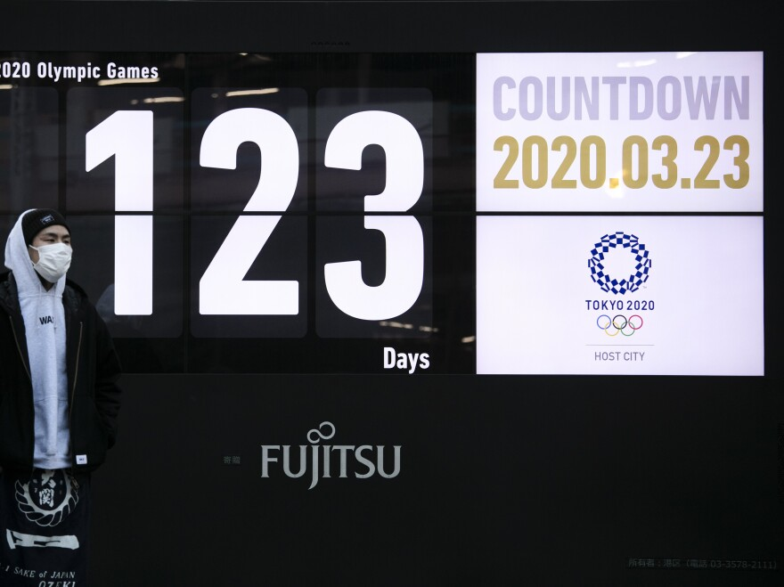 A man stands in front of a countdown display for the Tokyo 2020 Olympics and Paralympics in Tokyo, on Monday. Japan's Prime Minister Shinzo Abe acknowledged that a postponement of the crown jewel of the sporting world could be unavoidable.