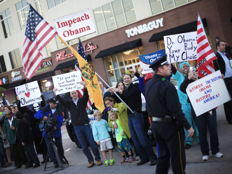 """People protest President Obama's """"If you like your insurance you can keep it"""" comment during a presidential visit to Dallas last week."""