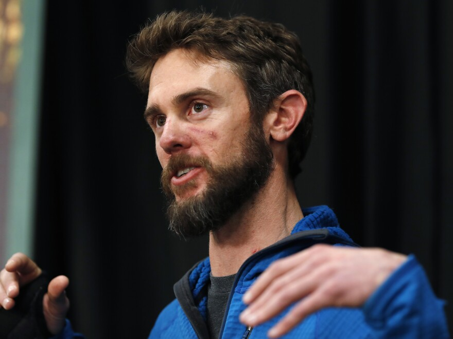 Travis Kauffman responds to questions during a news conference Thursday about his encounter with a mountain lion while running a trail just west of Fort Collins, Colo., this month.