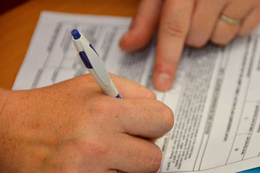 Hands signing a form