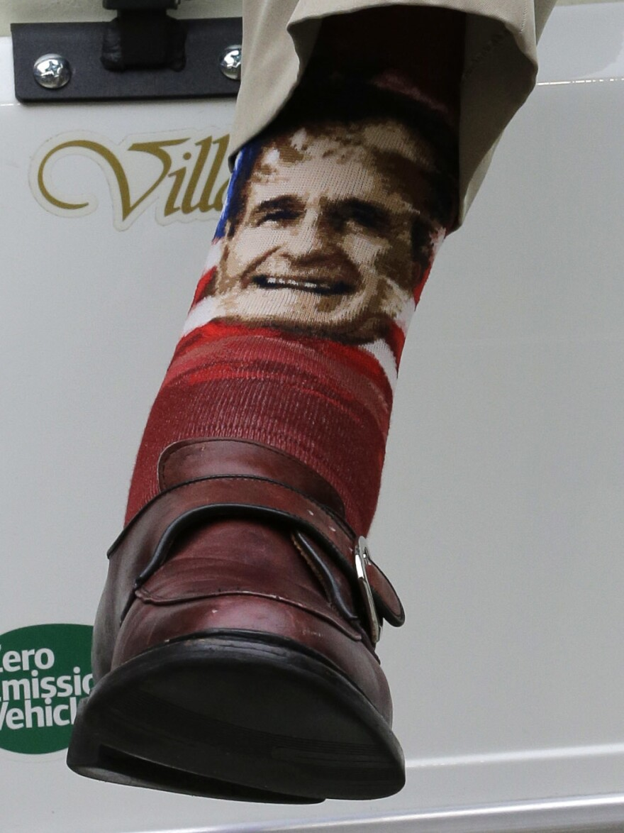 Bush wears socks with his image as he sits in a cart on the sidelines before an NFL football game between the New England Patriots and Houston Texans on Dec. 1, 2013, in Houston.