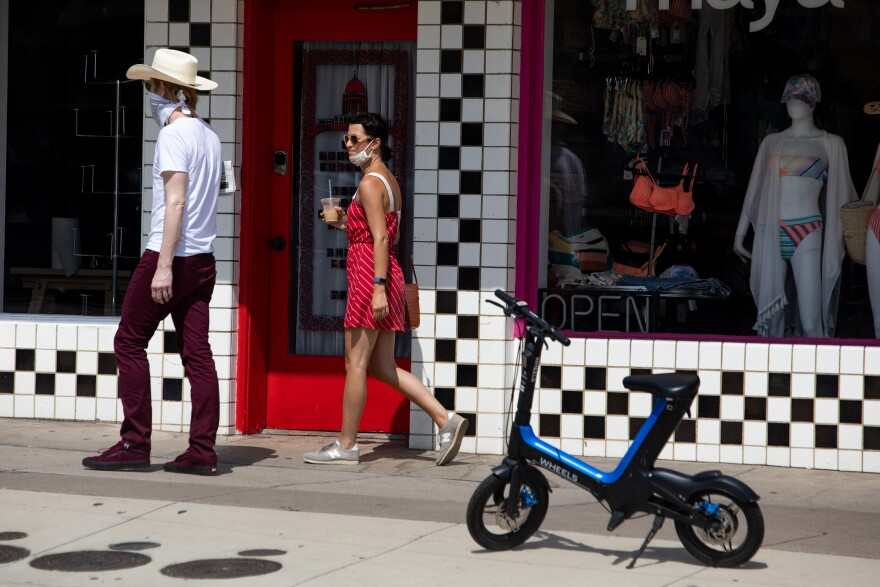 People wear face coverings while walking along South Congress Avenue on July 15.