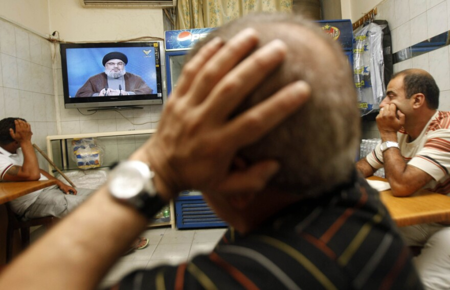 Lebanese men watch Hezbollah's leader Hassan Nasrallah give an address July 2. Nasrallah says authorities will never be able to arrest four members of his militant group who have been indicted in the murder of former Lebanese Prime Minister Rafik Hariri.