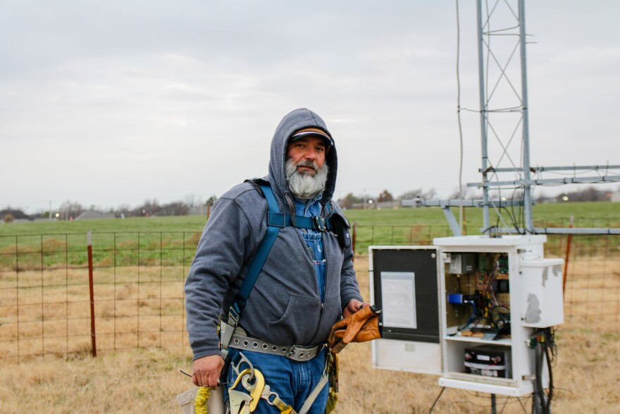 Meteorological Electronics Technician Kirk Wilson stands at the base of a 30-foot tower near Shawnee, Okla., after replacing a wind sensor that will feed data to the Oklahoma Mesonet.