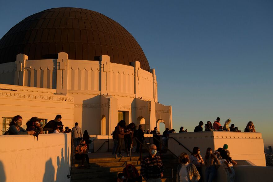 People watch the sunset as they wait to see the planets Jupiter and Saturn during the great conjunction at the Griffith Observatory in Los Angeles.