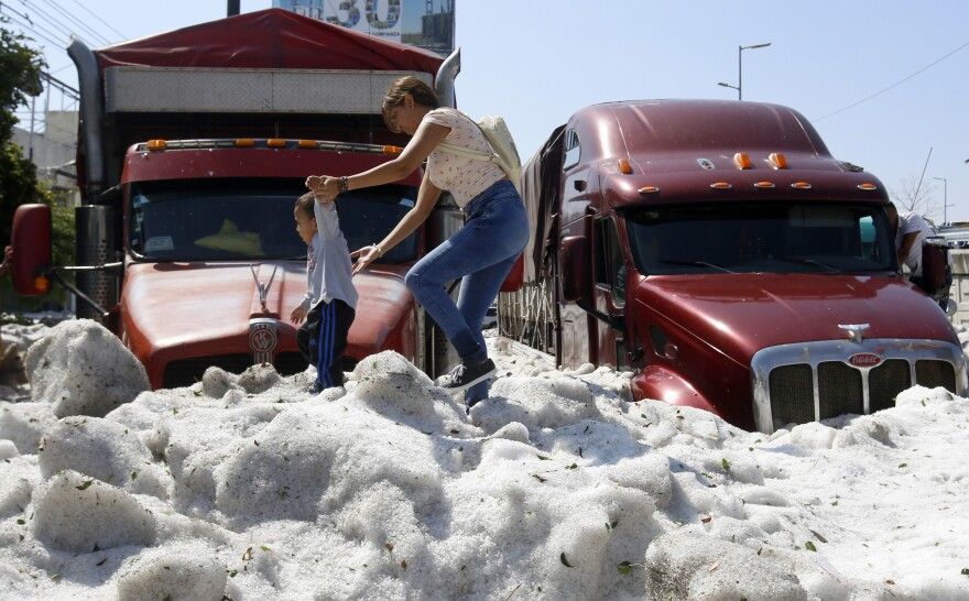 A woman and a child walk on hail in eastern Guadalajara on Sunday.