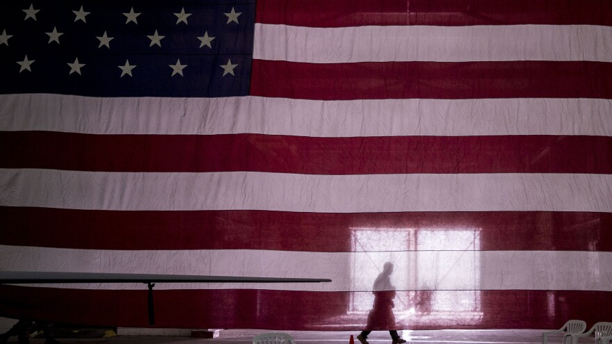 An American soldier carrying equipment walks past an American flag at Incirlik Air Base in Adana, Turkey, as U.S. Air Force war planes are used against ISIS.