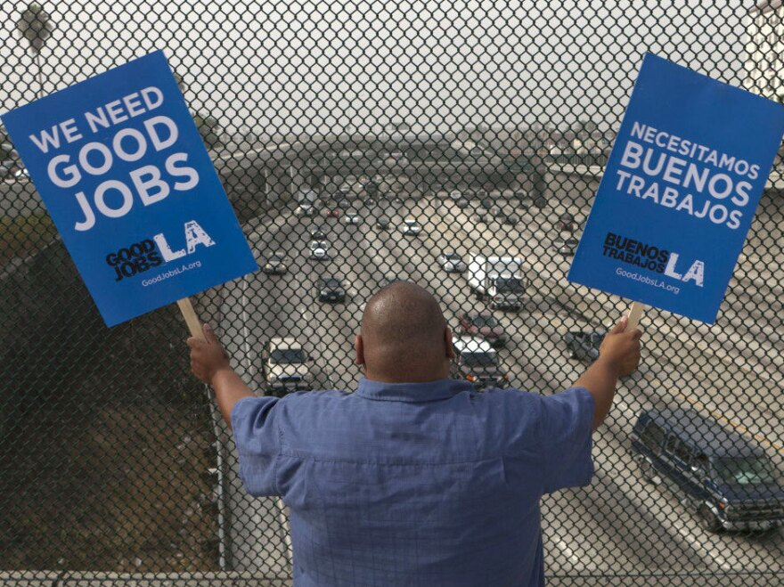 Los Angeles resident Christian Del Cid waves banners calling for jobs on a bridge over Interstate 110. Exactly three years after the  market crashed, some 14 million continue to look for work.